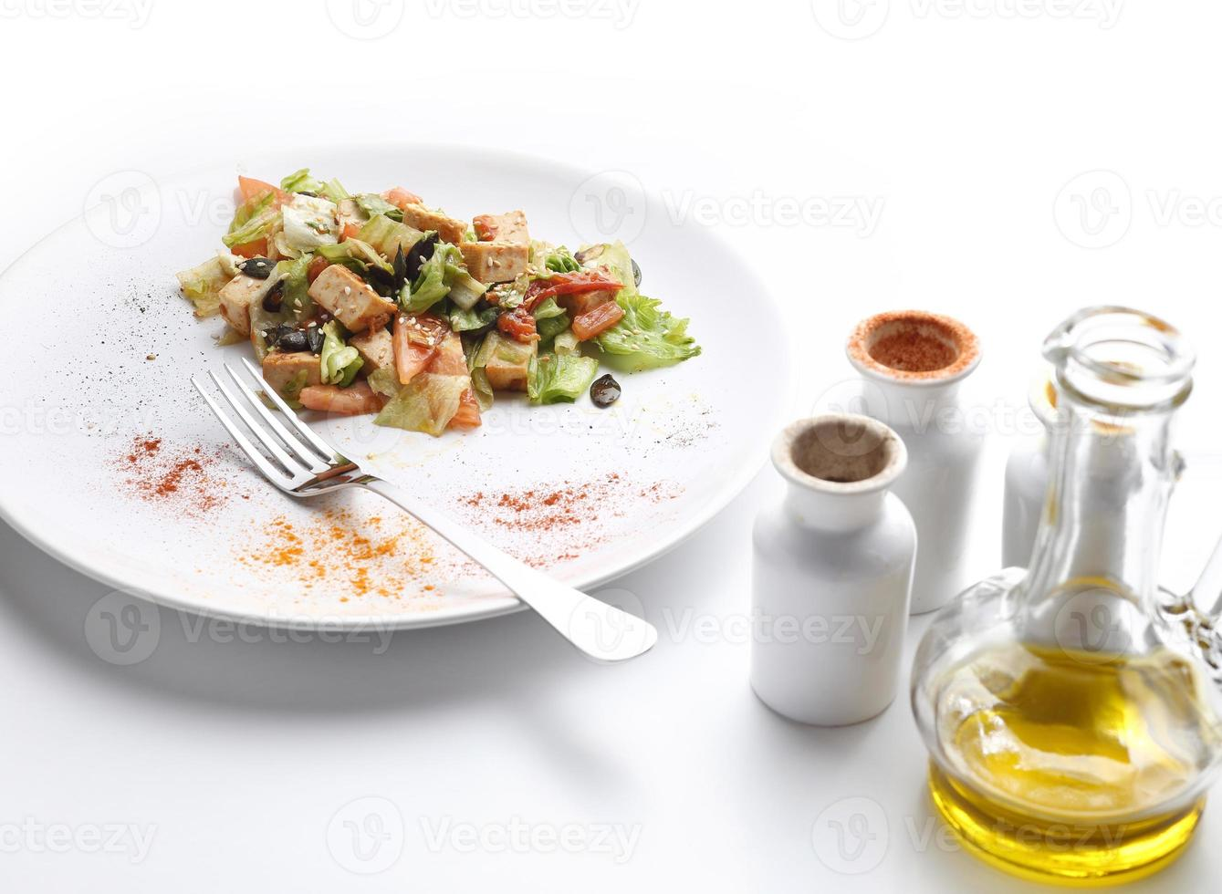 Tofu and vegetables salad. Olive oil and spices. White background photo