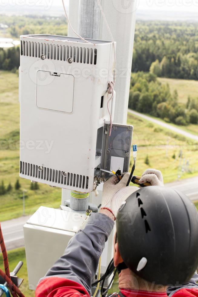 maintenance engineer repairing telecommunications equipment photo