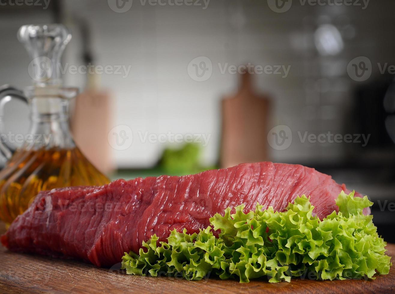raw beef on a cutting board with lettuce photo