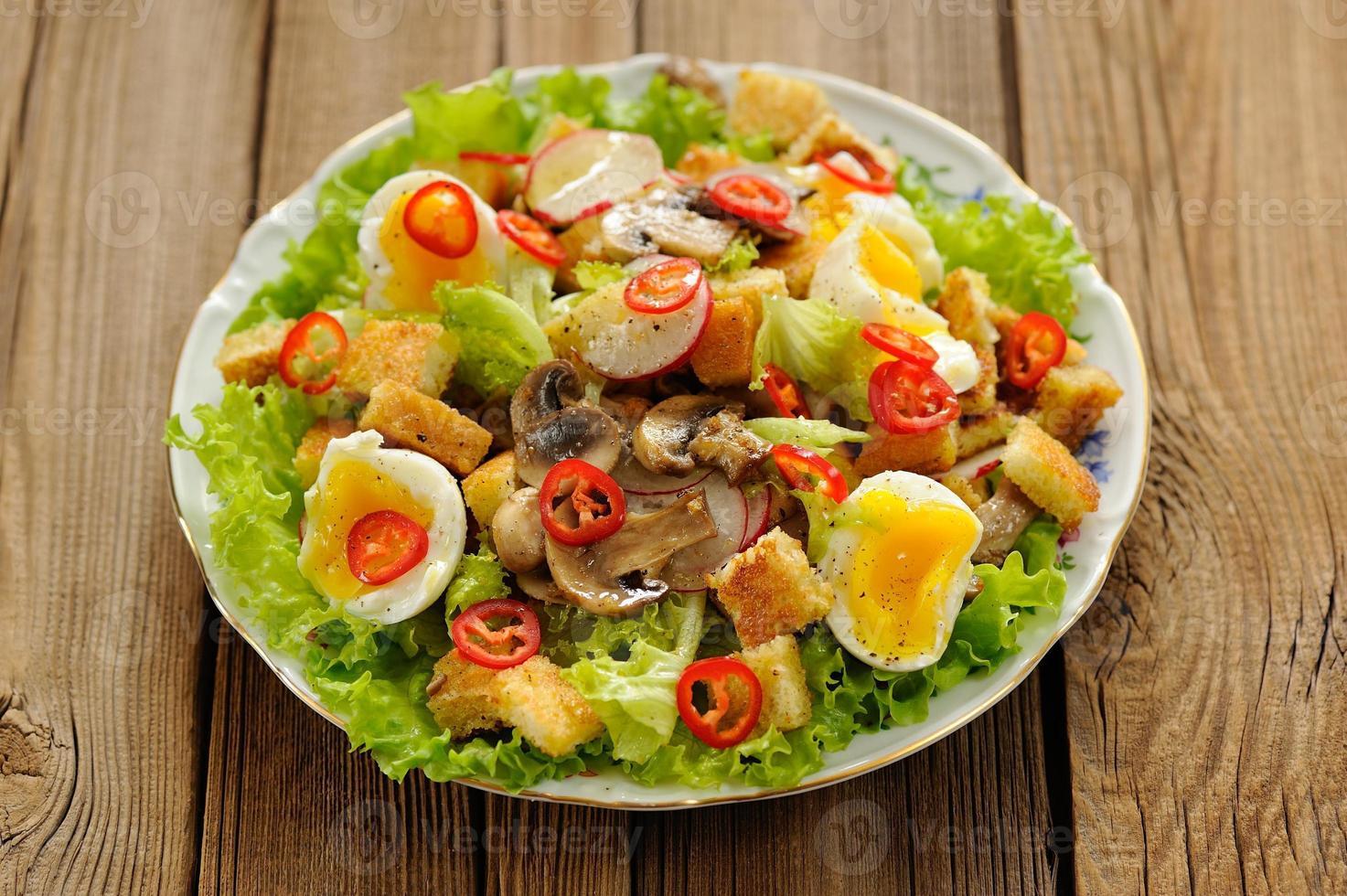 Ensalada César con champiñones, huevos, chile y rábano en madera foto