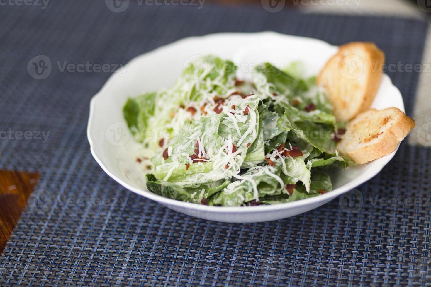 caesar salad with onion bread on blue matt photo