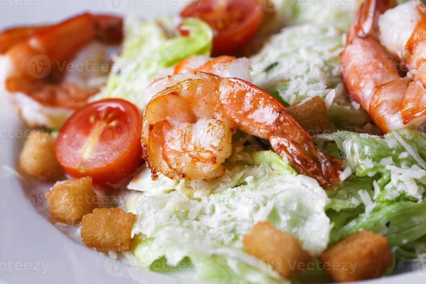 Caesar salad with shrimp on a plate photo