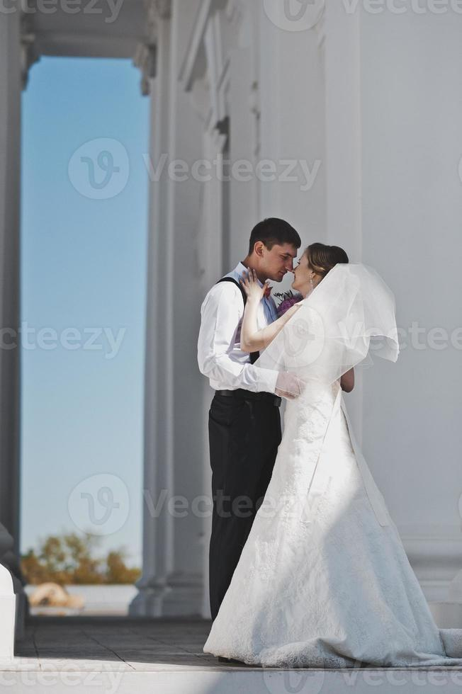 la pareja está parada frente a las columnas blancas foto