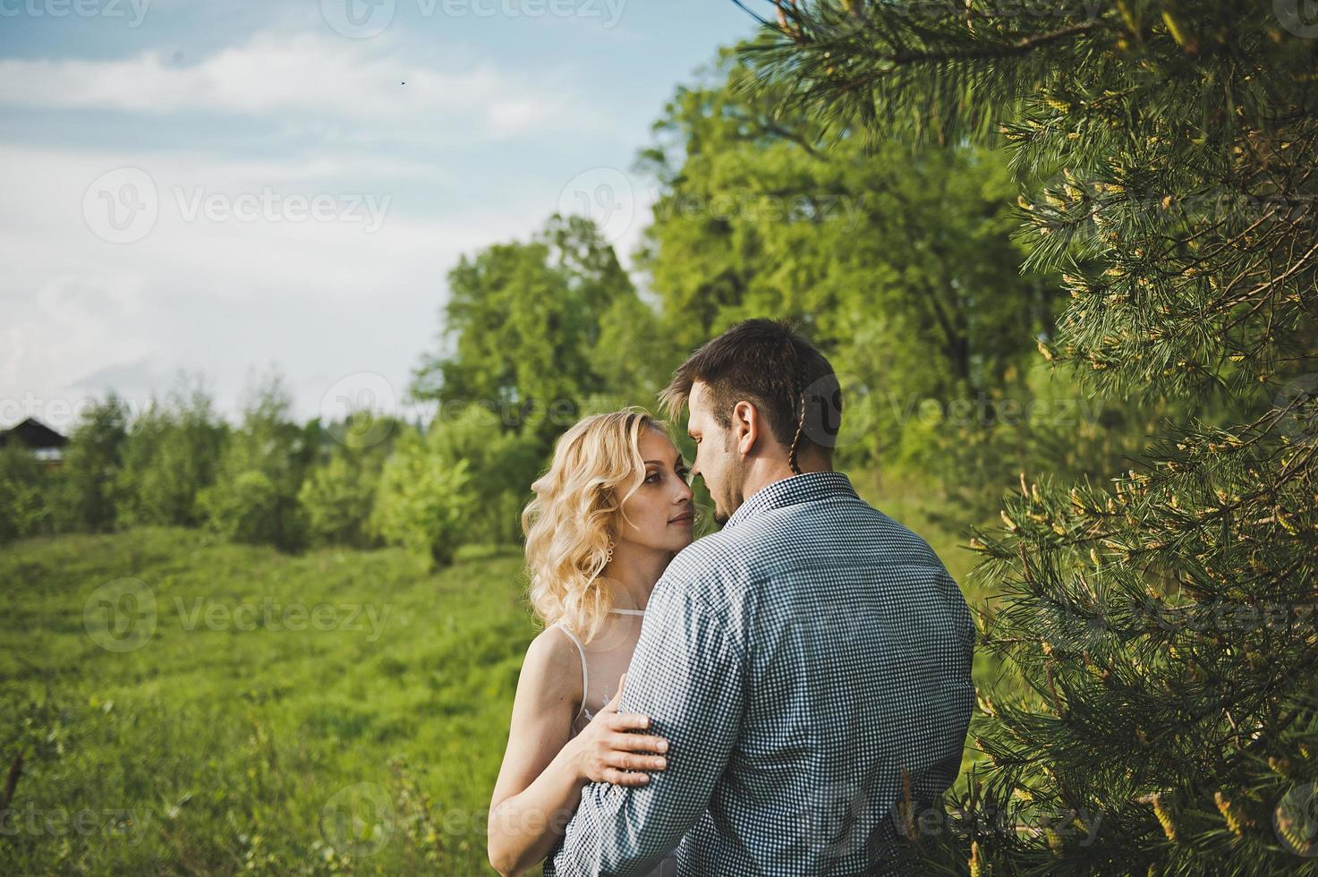 Newly-married couple in the wood about a tree photo