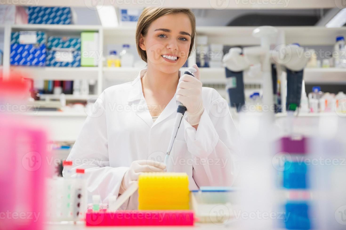Pretty science student using pipette photo