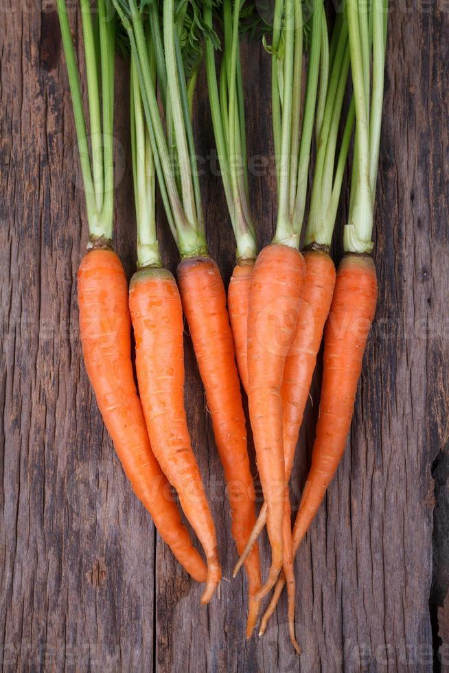 Bunch of fresh carrots with green leaves over wooden background photo