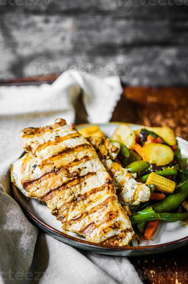 Grilled chicken with baked vegetables on rustic background photo
