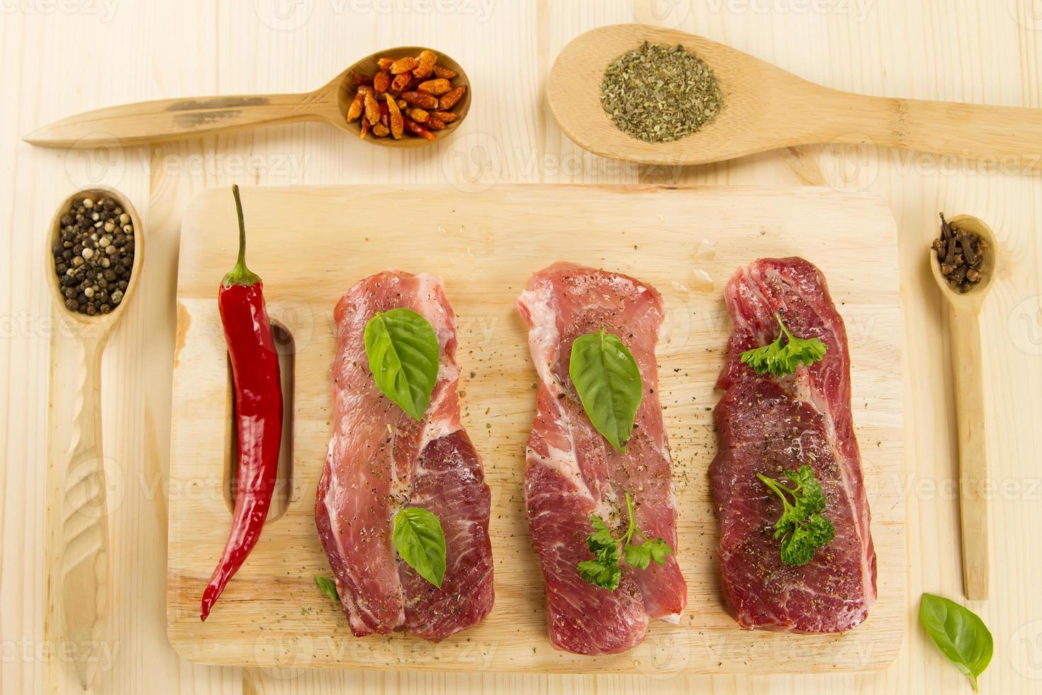 carne de cerdo cruda fresca en tabla de cortar con especias y hierbas foto