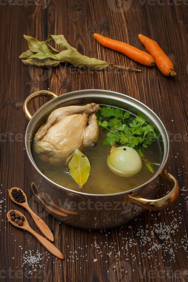 chicken broth with vegetables and spices in a saucepan photo
