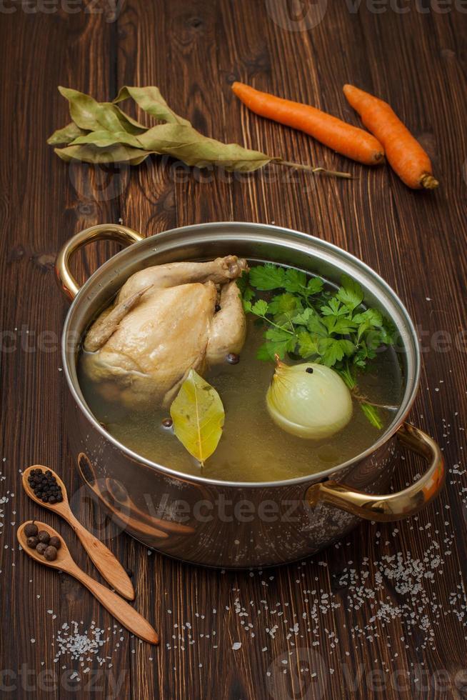 kippenbouillon met groenten en kruiden in een pan foto