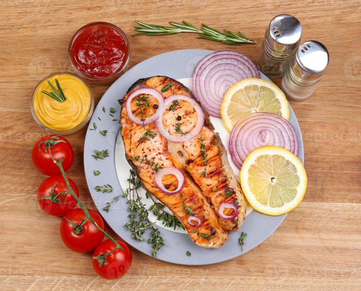 saboroso salmão grelhado com legumes, na mesa de madeira foto