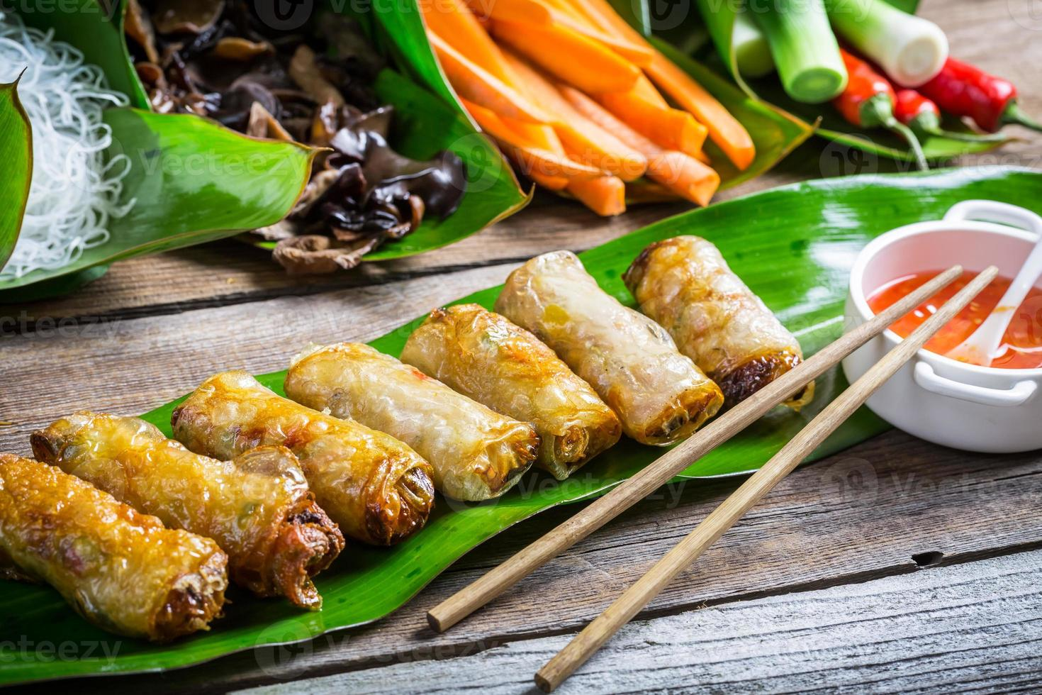 Fried spring rolls surrounded by ingredients photo