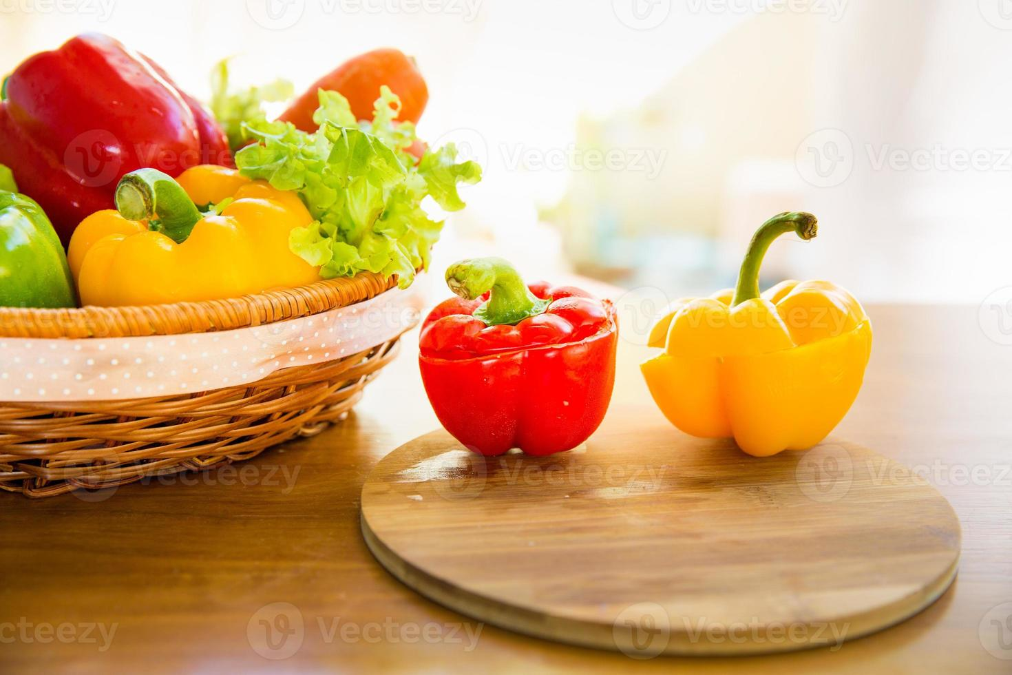 Bell pepper on chopping block with healthy vegetable in basket photo