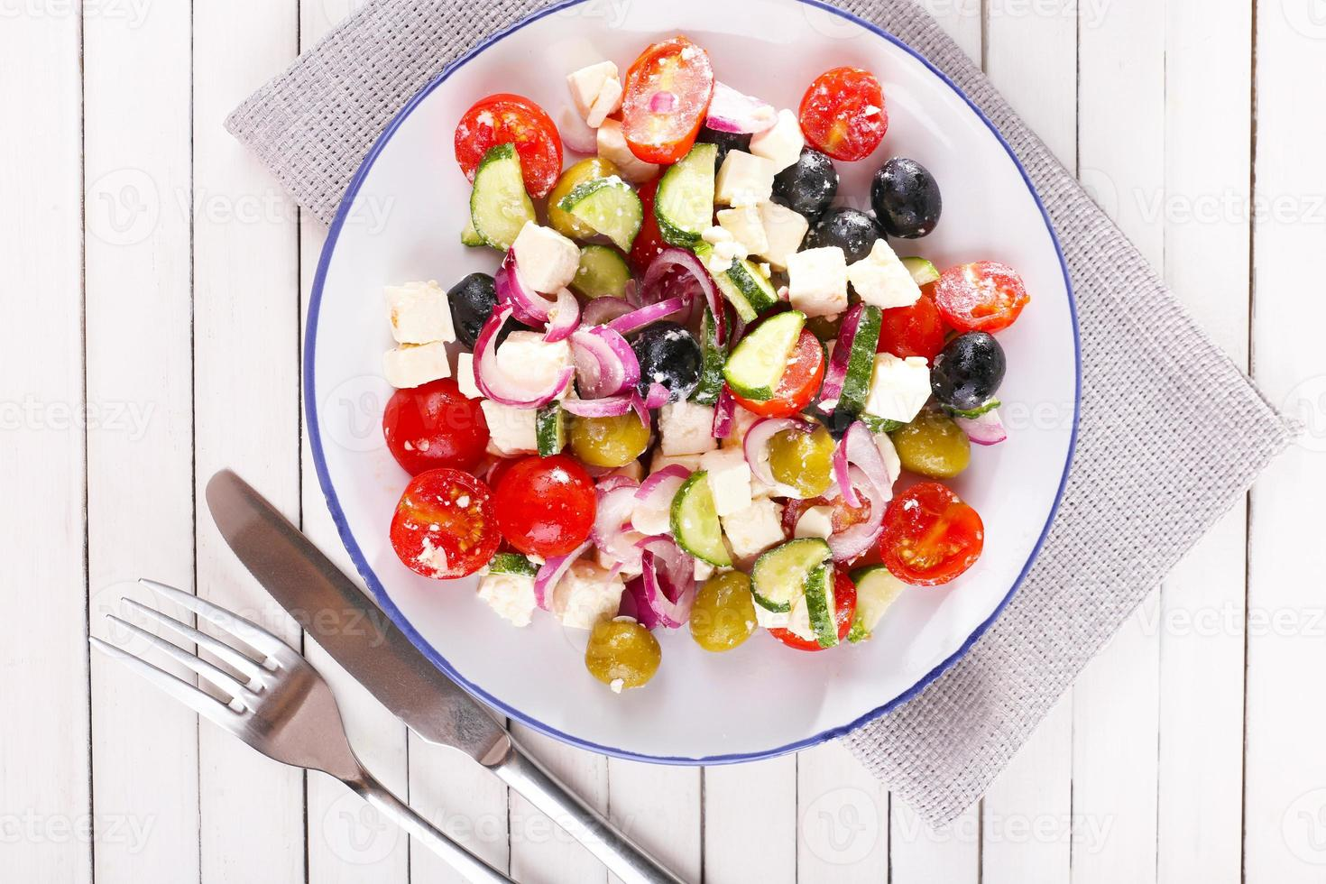 Greek salad served in plate on napkin on wooden background photo