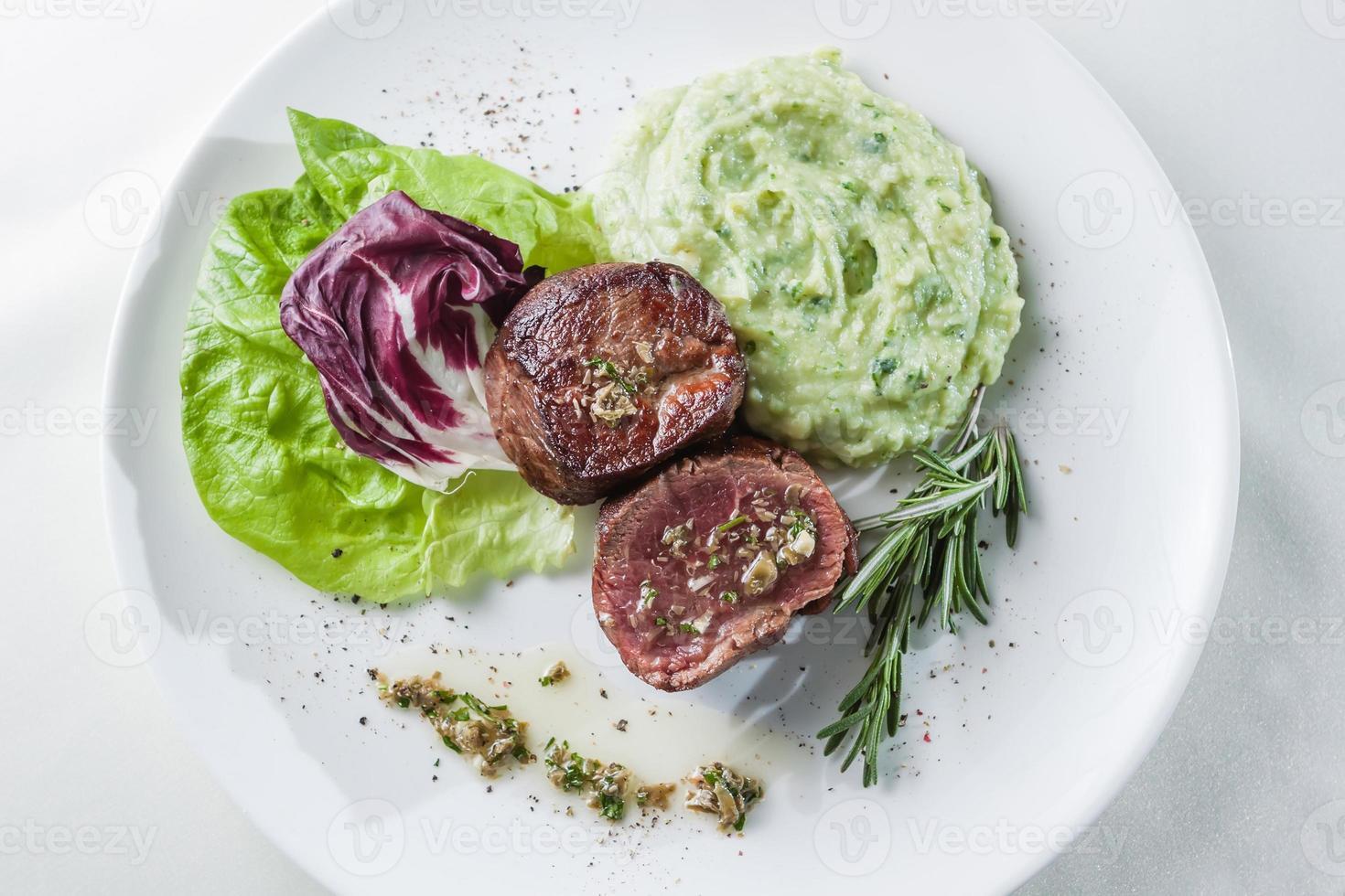 roast steak with lettuce, rosemary and mashed potatoes photo