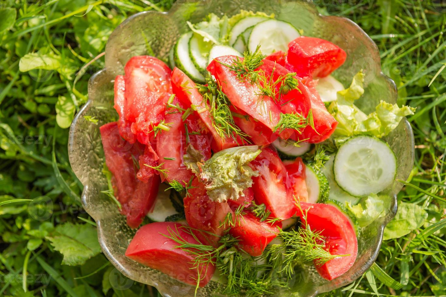 lettuce, tomatoes and cucumbers in a glass bowl photo