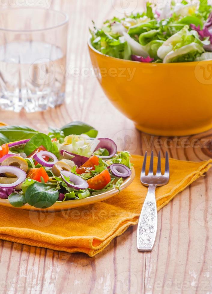 Vegetarian salad with lettuce, tomatoes, olives and onions photo