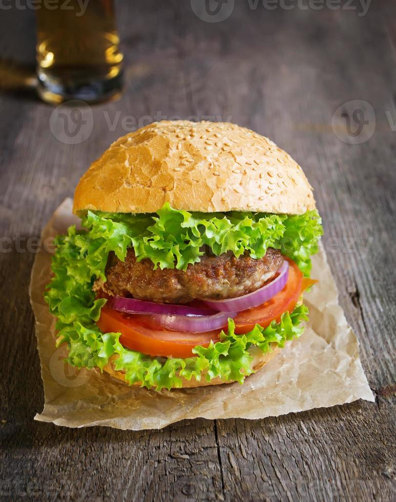 Burger with beef cutlet, lettuce, onions and tomato photo