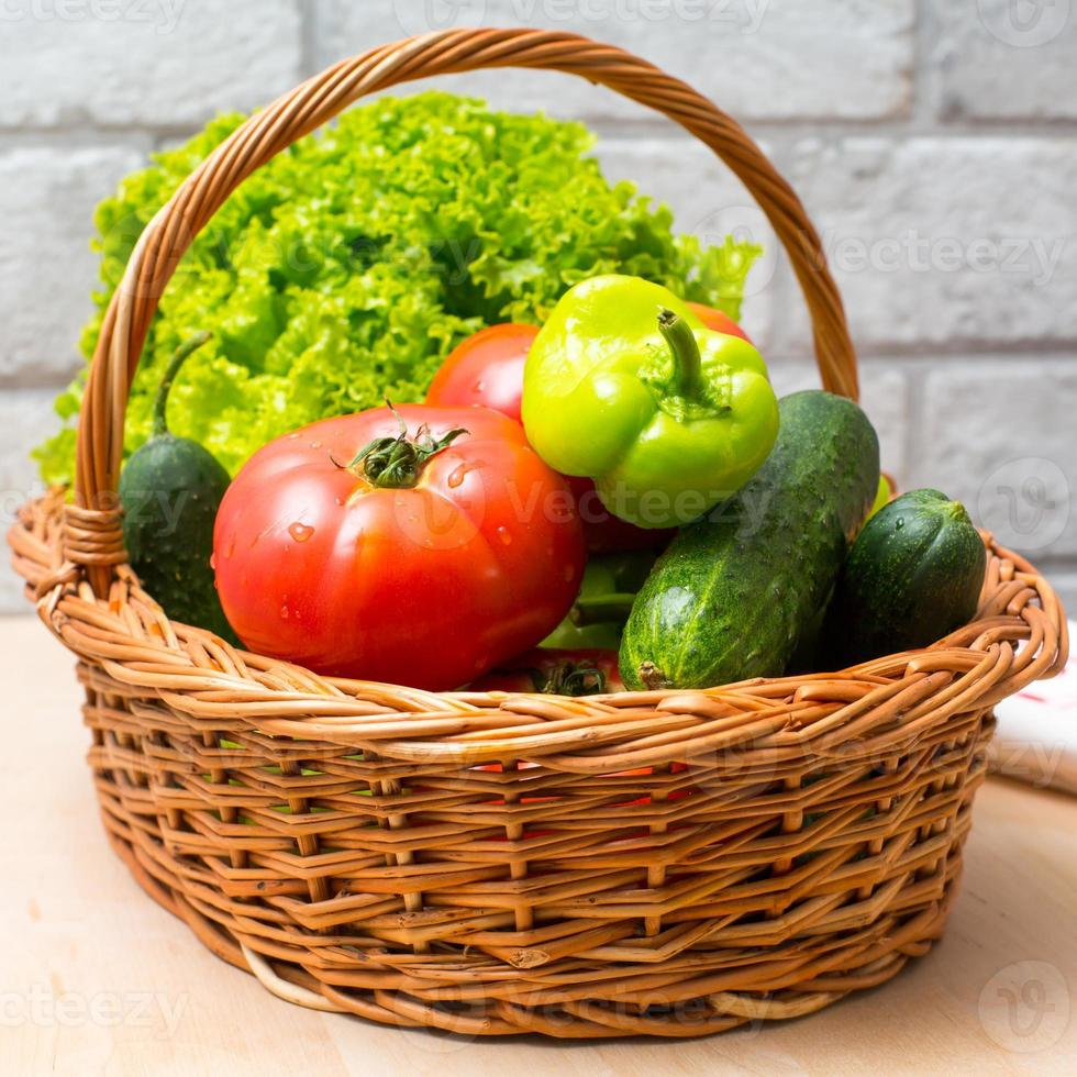 Fresh vegetables in basket. Tomato, cucumber, pepper and lettuce photo