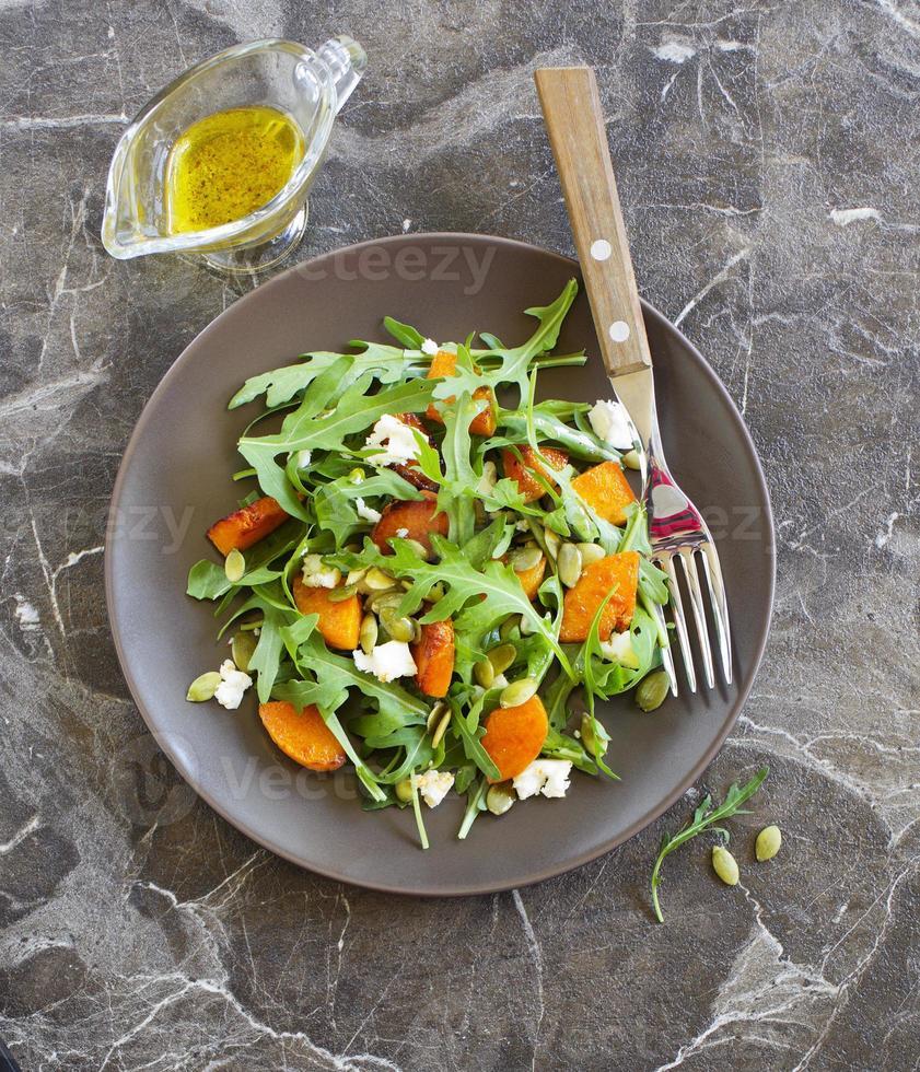 Pumpkin salad, arugula and feta. photo