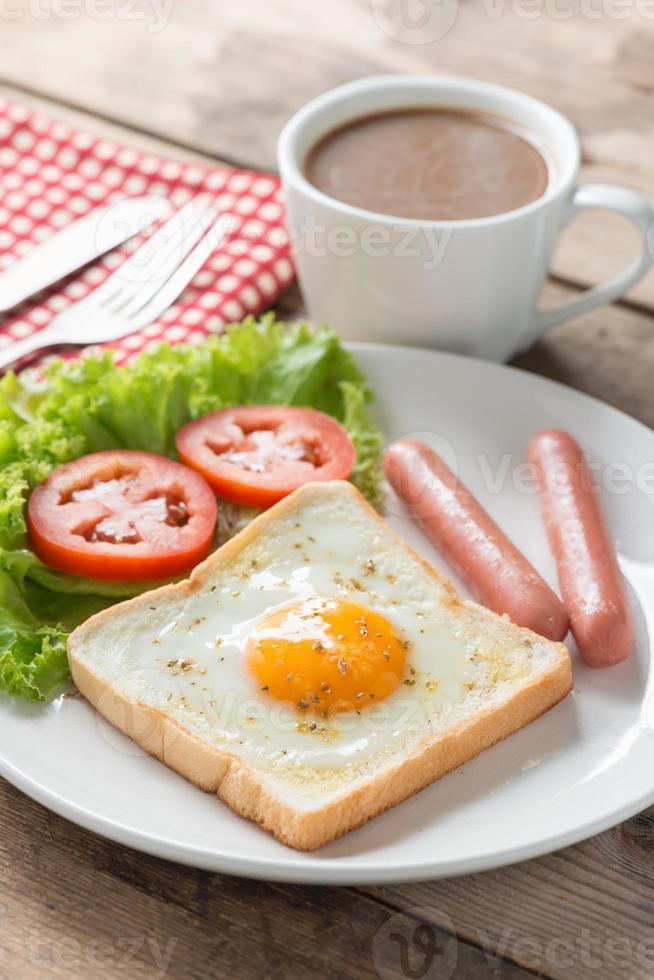 Desayuno, huevo en un hoyo con salchichas y café. foto