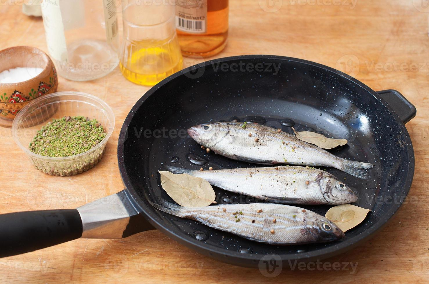fishes with spices on a frying pan on wooden background photo