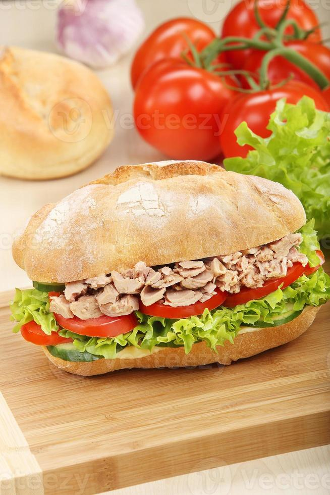 Sandwich with tuna on wood background photo