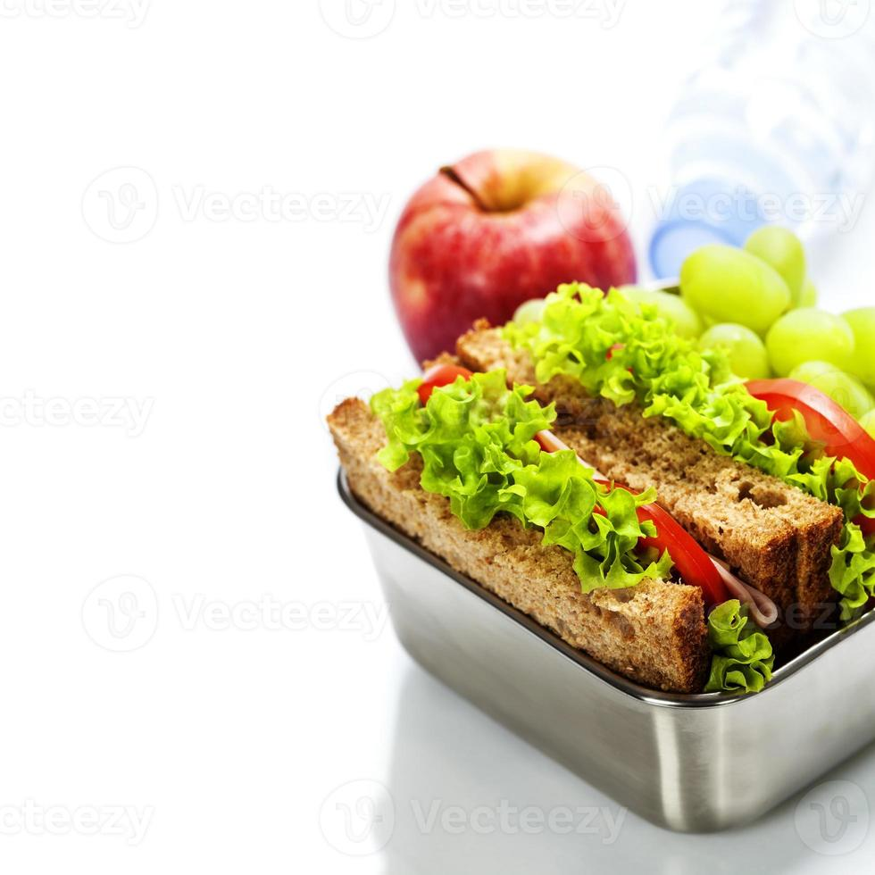 Lunch box with sandwiches and fruits photo