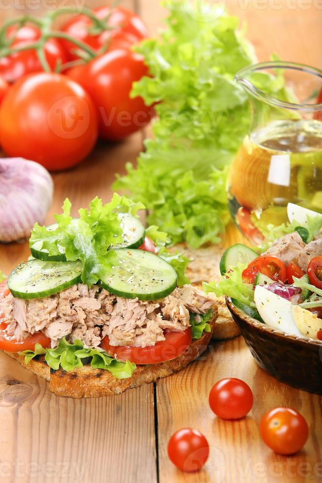 sanduíche com atum e salada em fundo madeira foto