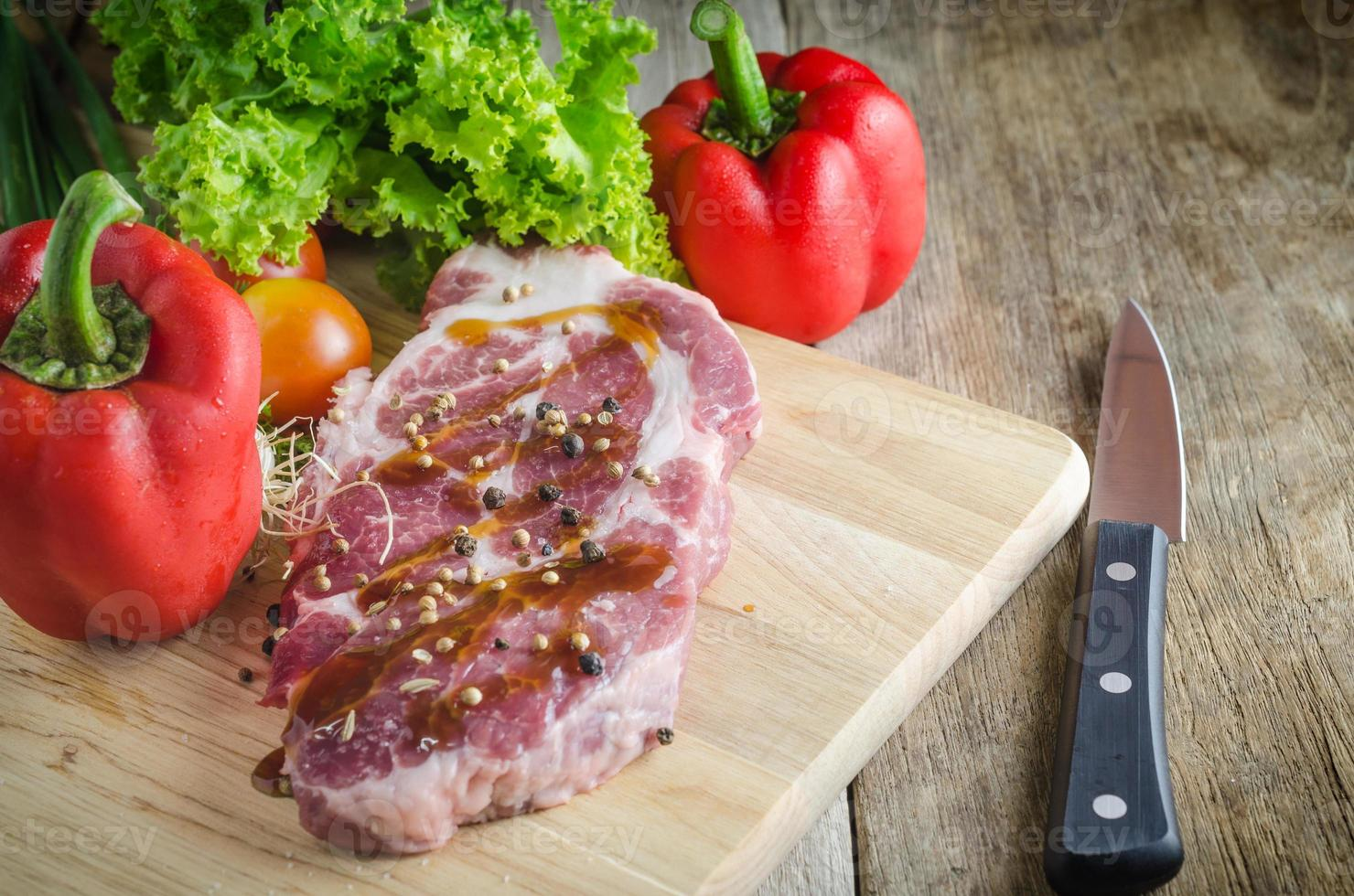 Raw pork on cutting board and vegetables knives. photo