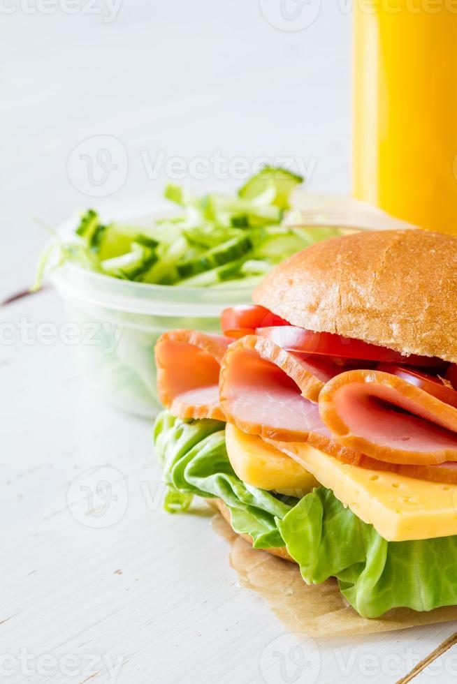 Sandwich, salad, juice, white wood background photo