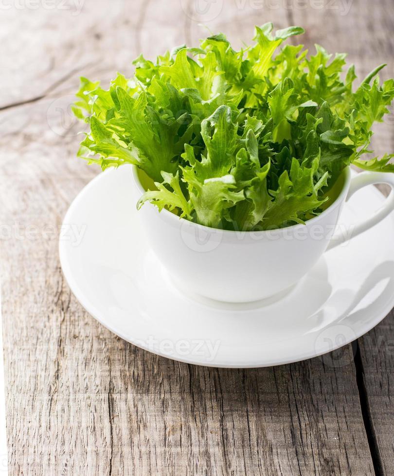 tazón de rúcula verde fresca y natural en una taza blanca sobre foto