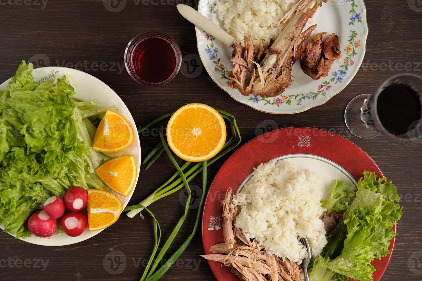 Dinner od turkey meat with rice, lettuce salad with radish photo