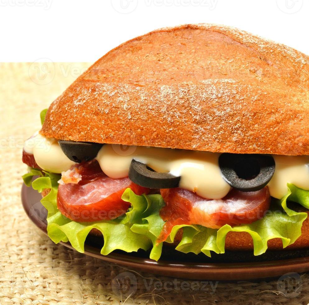 saboroso sanduíche fresco com alface verde, presunto, azeitonas na demissão foto