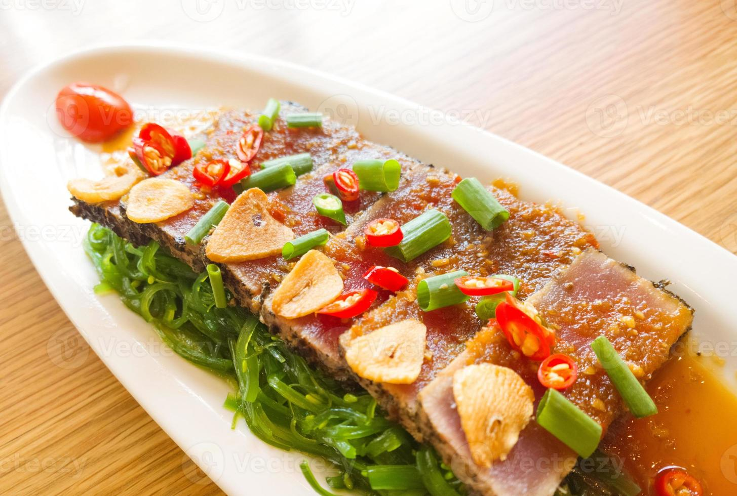 smoke tuna spicy with salad frieze on wooden table photo