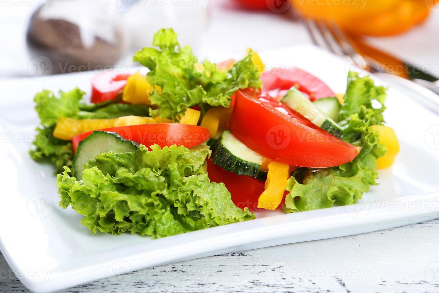 Fresh vegetable salad on white wooden background photo