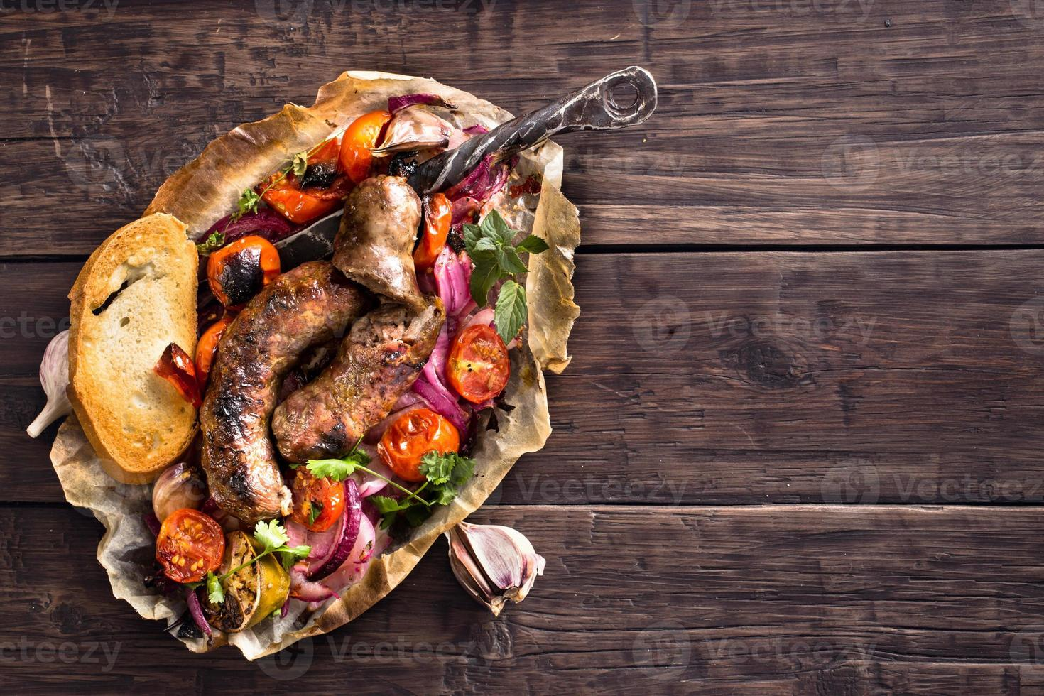 Rustic homemade sausages with onion and tomatoes on table photo