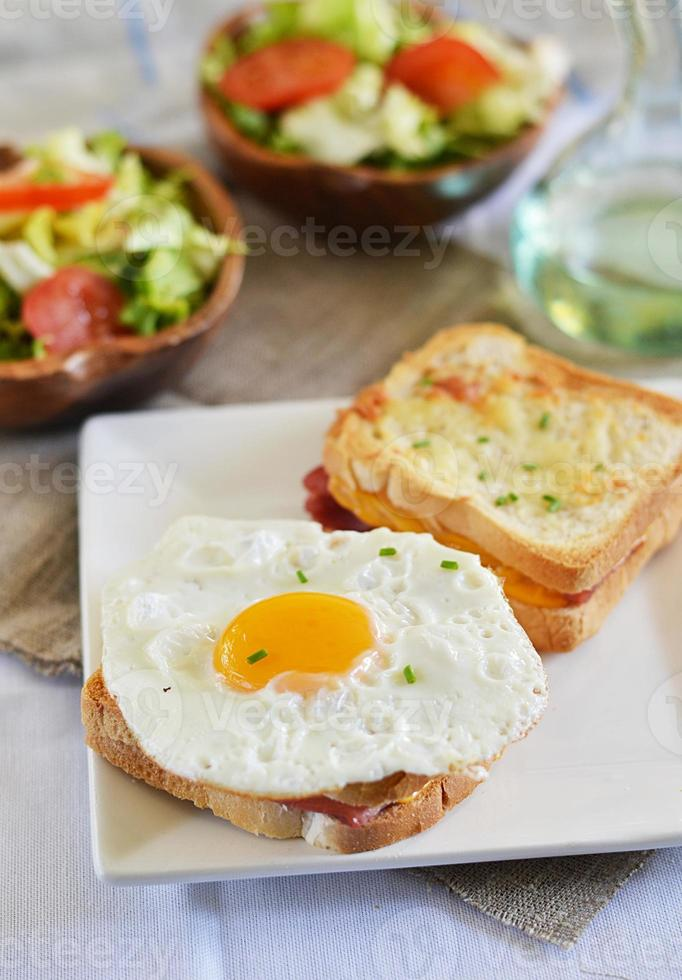 Croque monsieur and croque madame with green salad photo