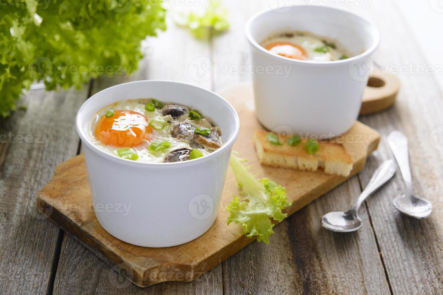 Baked eggs with mushrooms, cream and chives photo