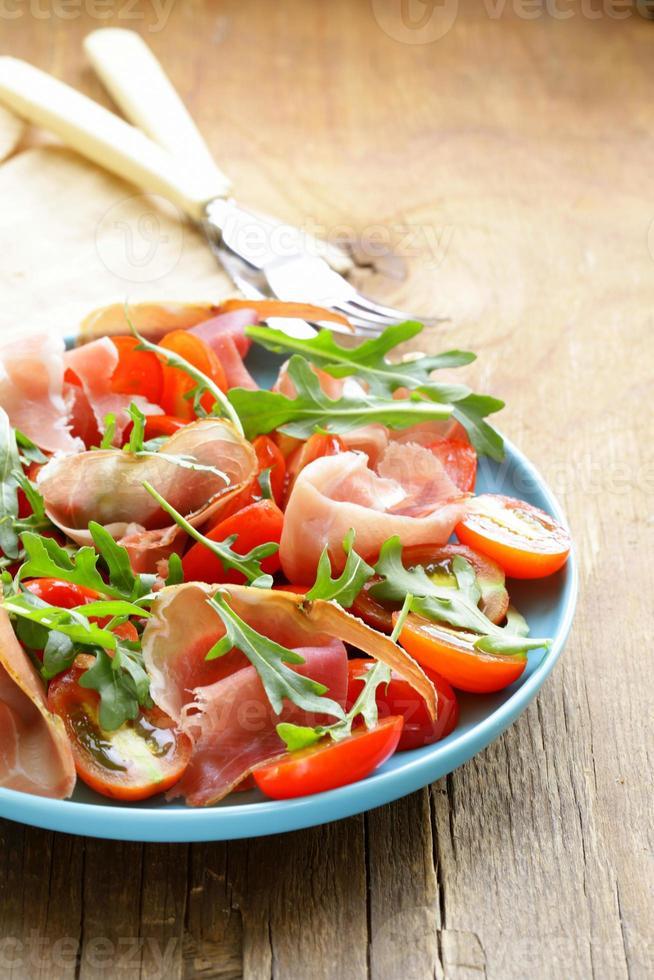 salad with parma ham (jamon), tomatoes and arugula photo