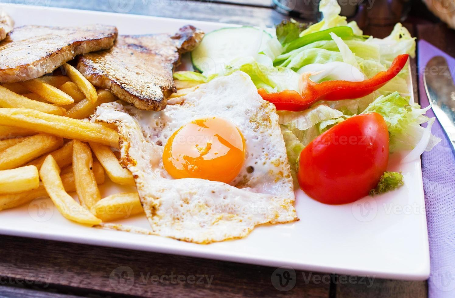 Fried egg with potato fries, grilled steak. photo