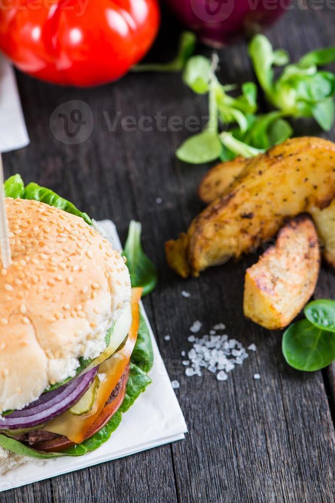 Sirviendo hamburguesas caseras con patatas wegdes en mesa de madera foto