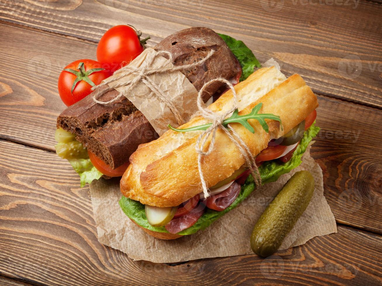 Two sandwiches with salad, ham, cheese and tomatoes photo