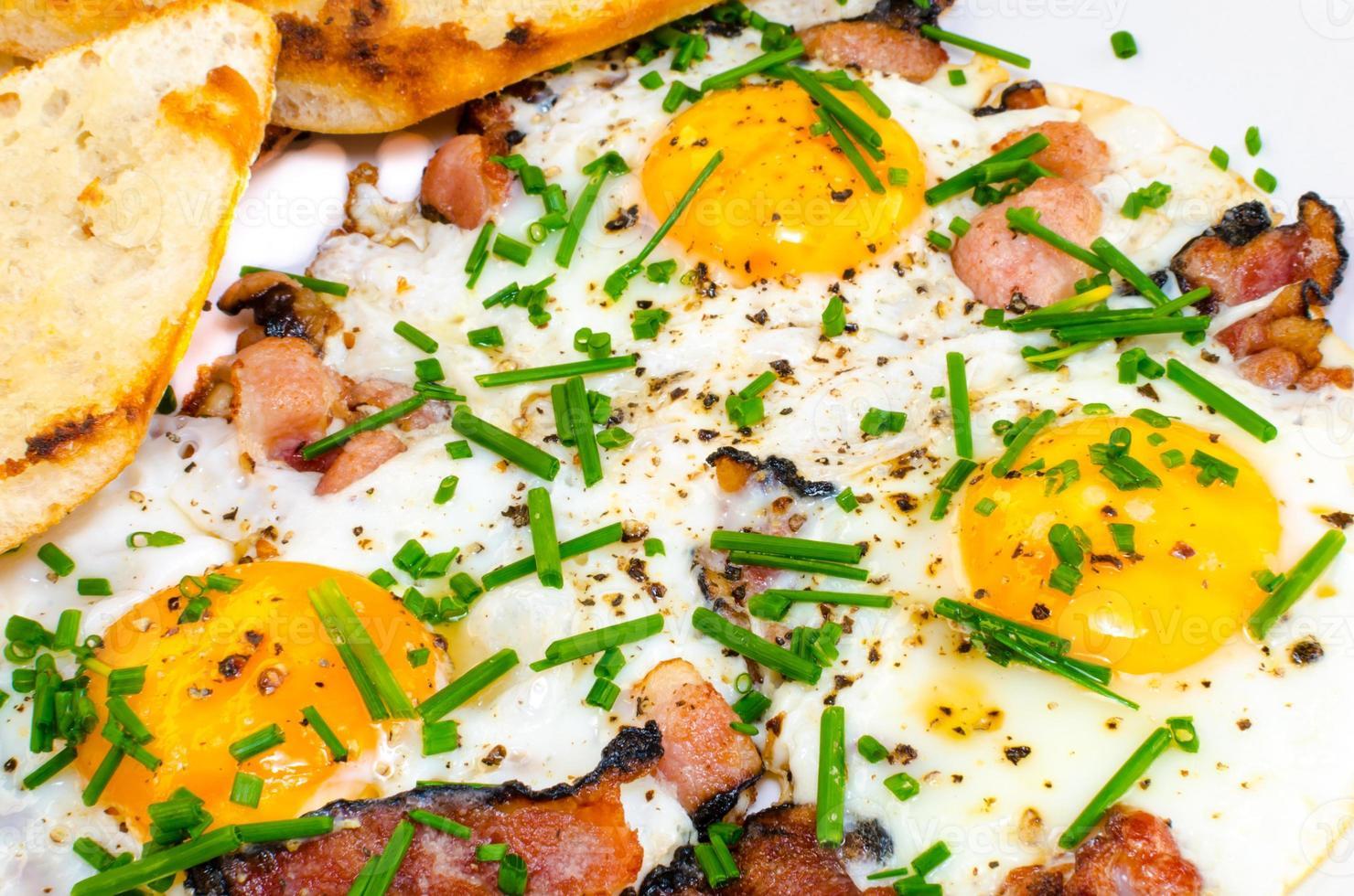 tocino, huevos y cebollino con tostadas crujientes foto