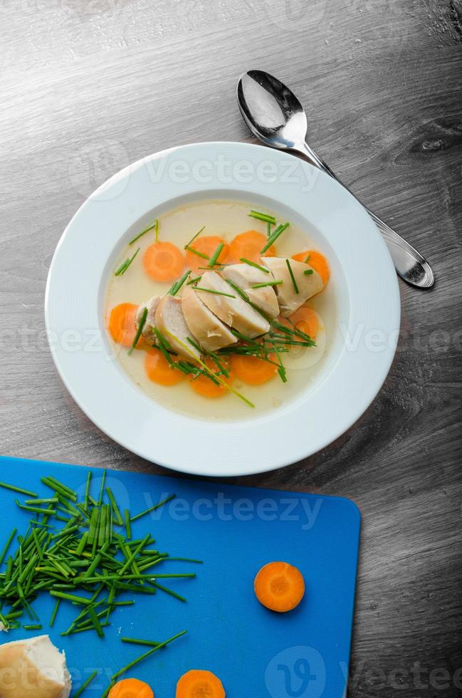 Chicken broth with fresh vegetables photo
