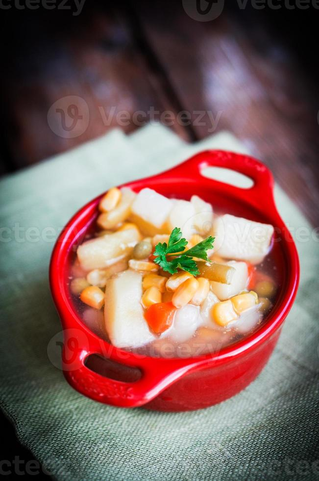 Chicken noodle soup with vegetables in bowl on rustic table photo