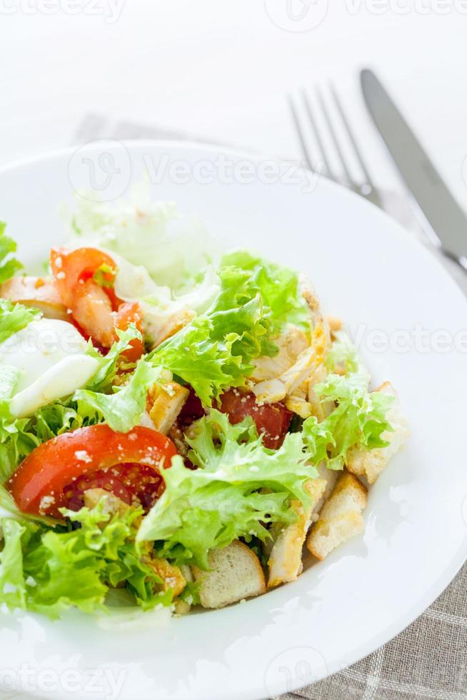 Caesar salad with chicken, cherry tomatoes, lettuce photo