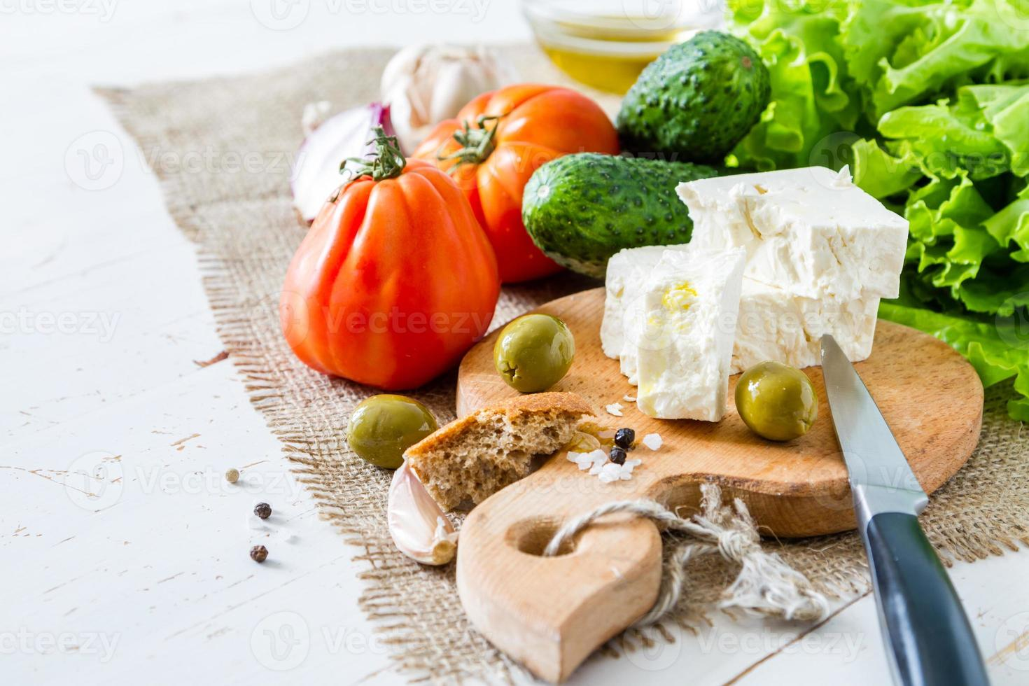 Salad ingredients - tomato, lettuce, cucumber, feta, onion, olive, garlic photo
