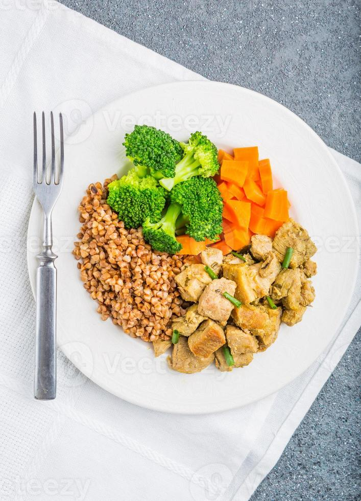 Buckwheat with meat and vegetables ona white plate photo