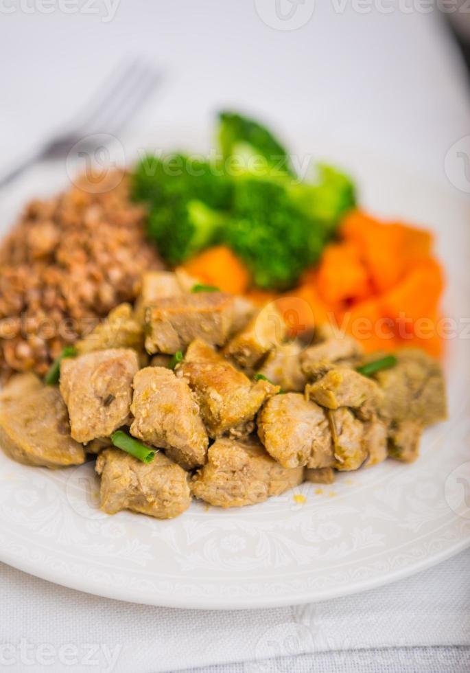 trigo sarraceno con carne y verduras en un plato blanco foto